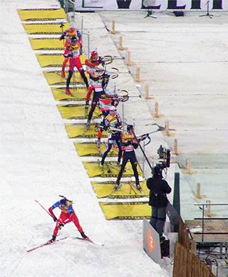 Biathletes in the shooting area of a competition